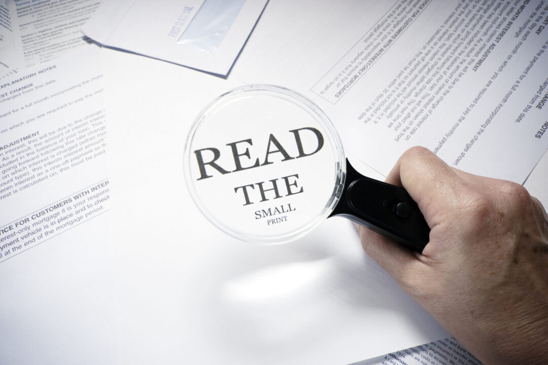 "magnifying glass over document ""read the fine print"""