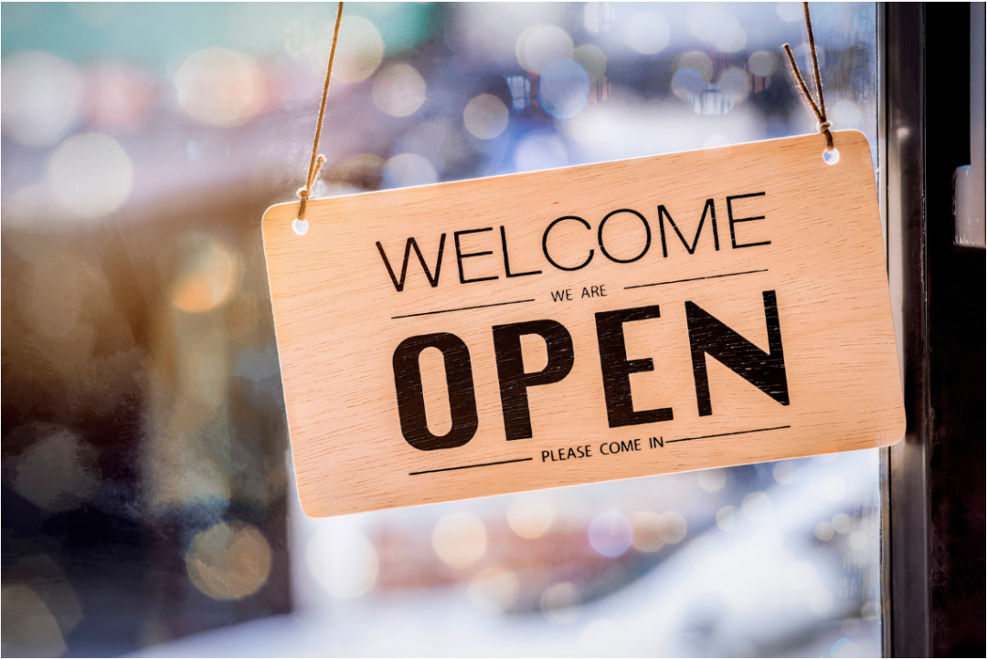 hanging welcome we are open sign on business window