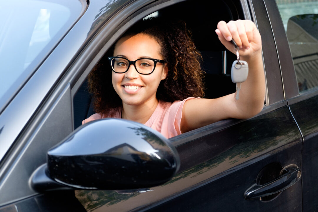 A smiling female teen driver sits in her car and holds up car keys happy about lower insurance costs