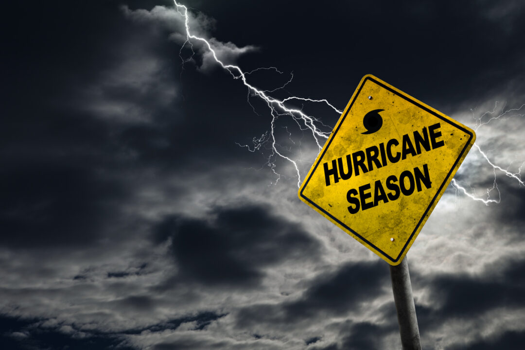 A yellow sign with hurricane season on it in a lightning storm