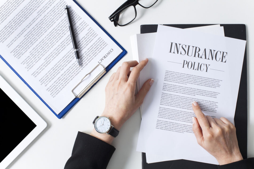 A bird's eye view of a woman reading an insurance policy with insurance terms