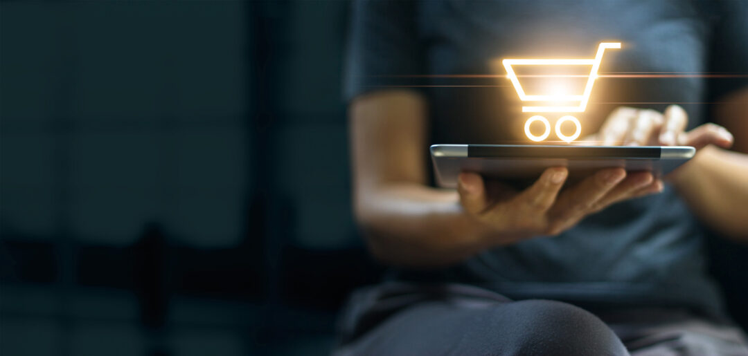 A woman sits with a laptop on her lap and a glowing, digital shopping cart above it and needs commercial insurance for her e-commerce business
