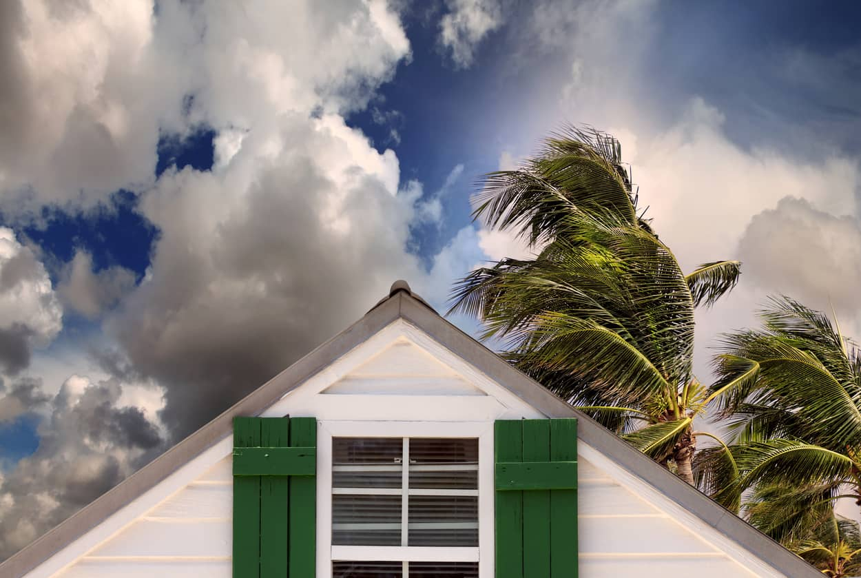 Closeup rooftop of a wooden house in a storm needs hurricane preparedness and insurance