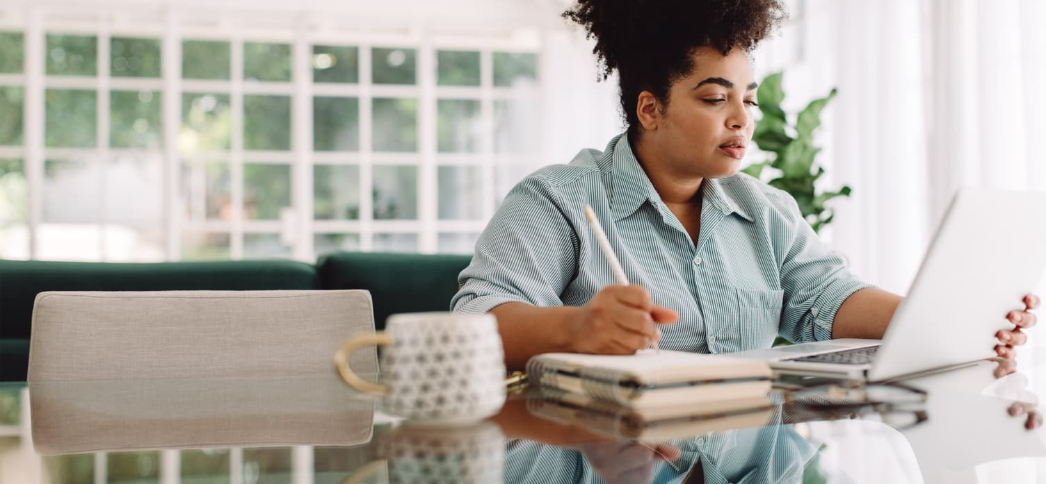 A businesswoman taking notes and using a laptop needs self-employment insurance