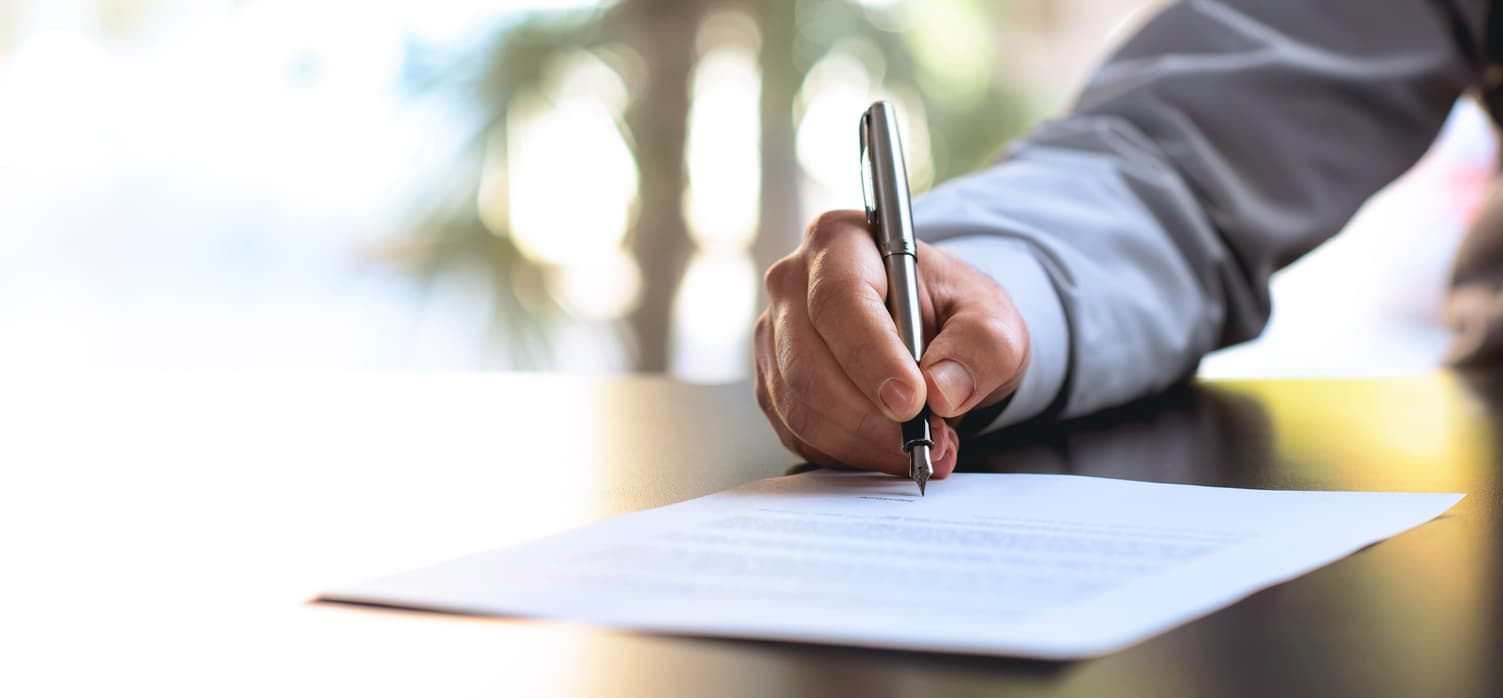 A hand signing a contract that is insurance for IT professionals