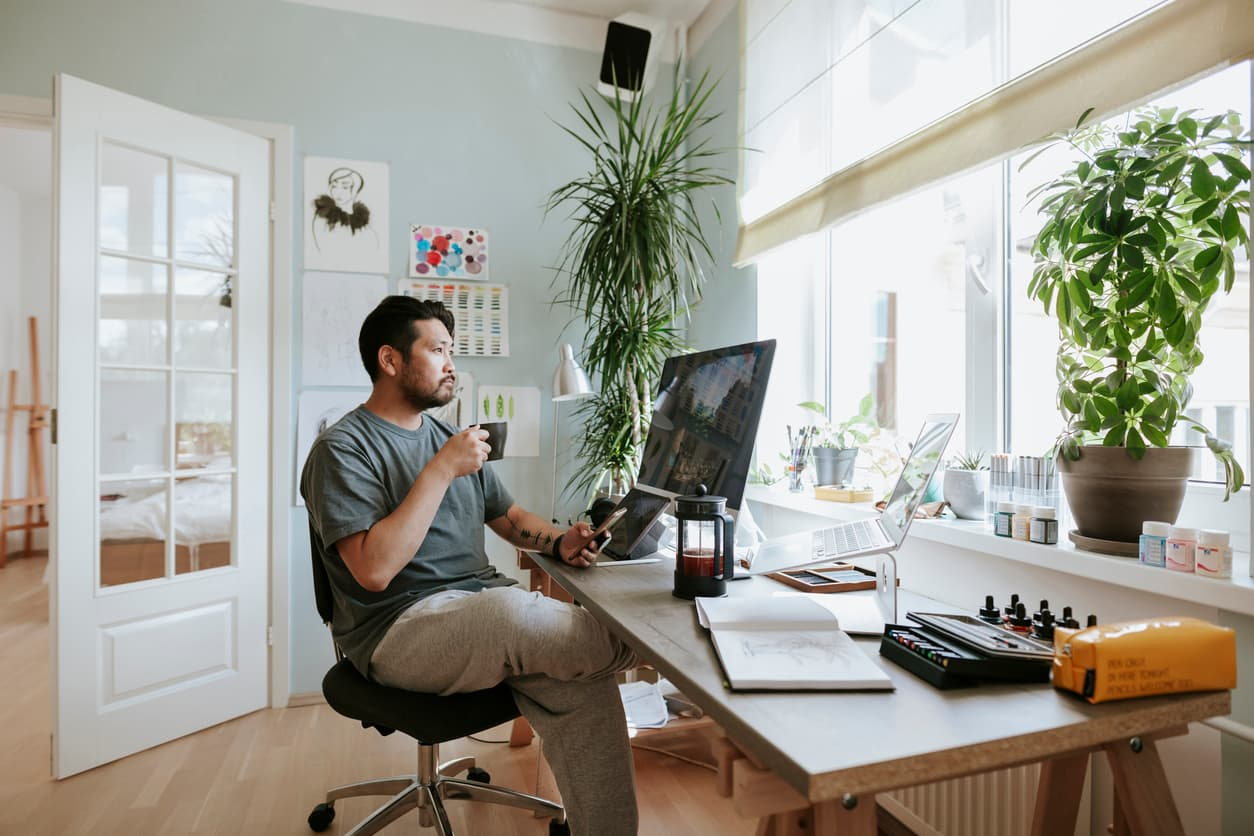A man sits in his remote work office, covered by a commercial insurance policy
